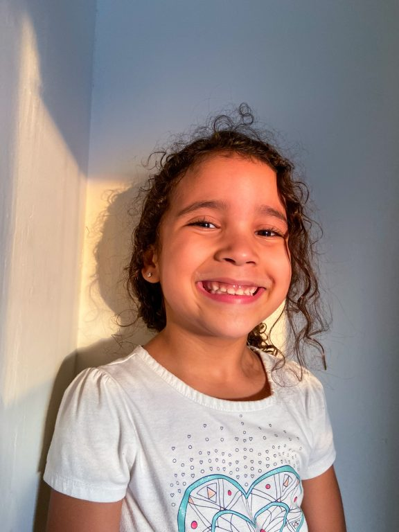 a young girl with curly hair smiles at the camera