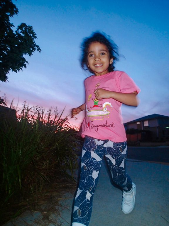a sunset, a young girl wearing a pink shirt and blue leggings runs and smiles