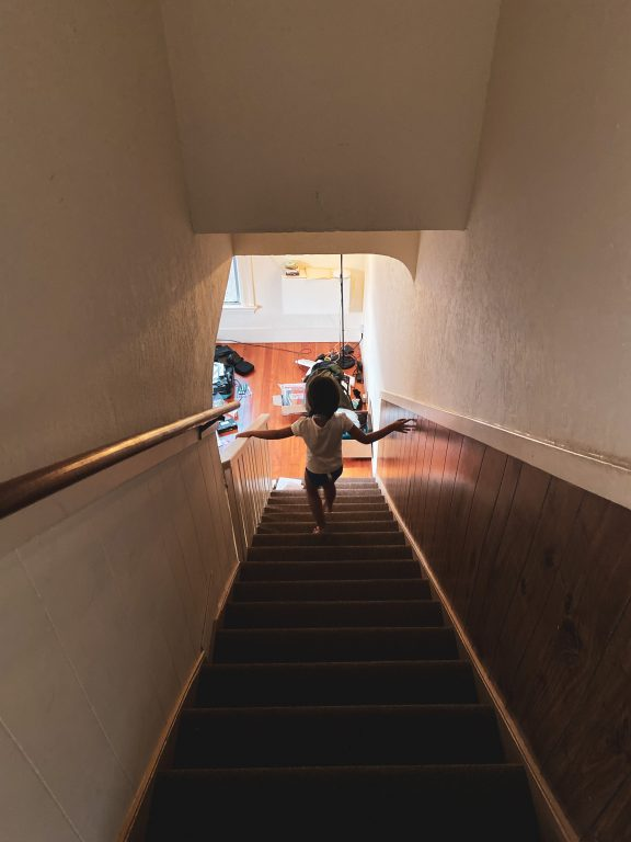 a young girl walks down the steps from an apartment