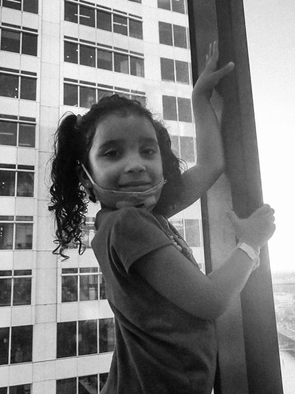 a black and white photo of girl in curly pigtails in front of big hotel window