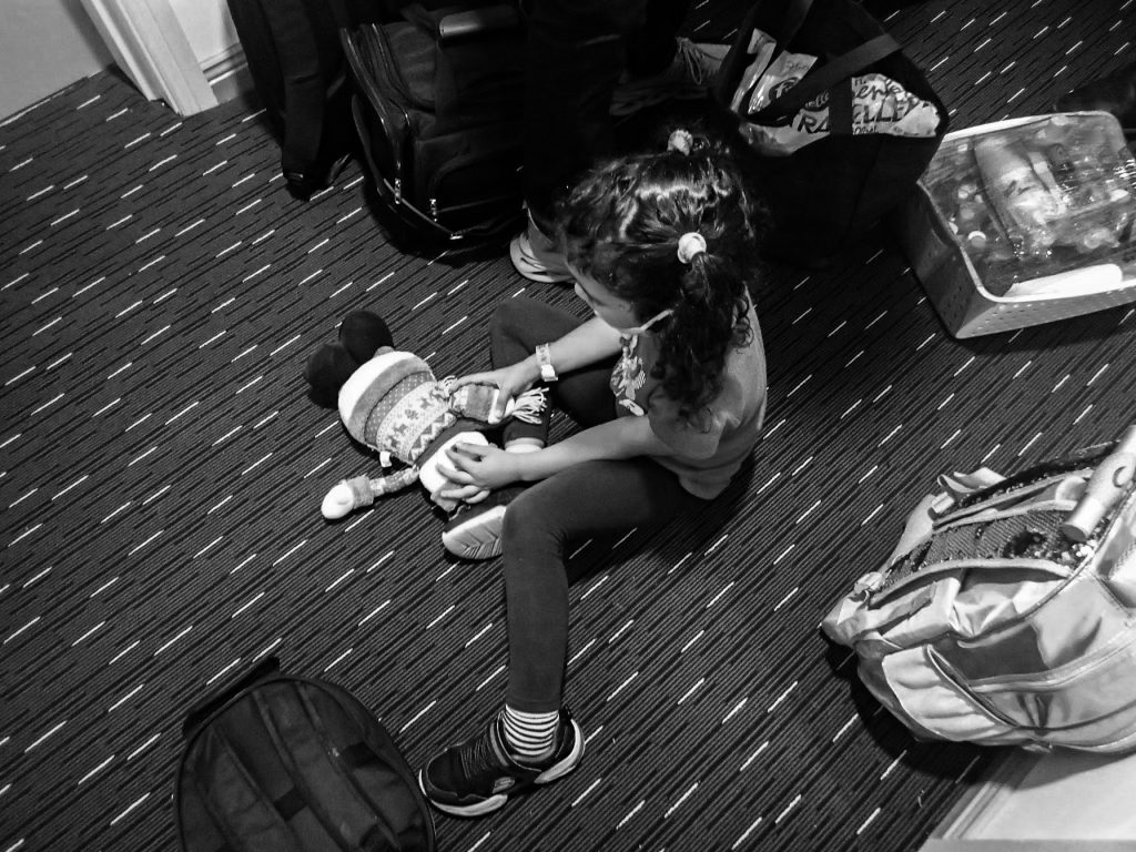 a black and white photo of young girl playing on the floor with a doll