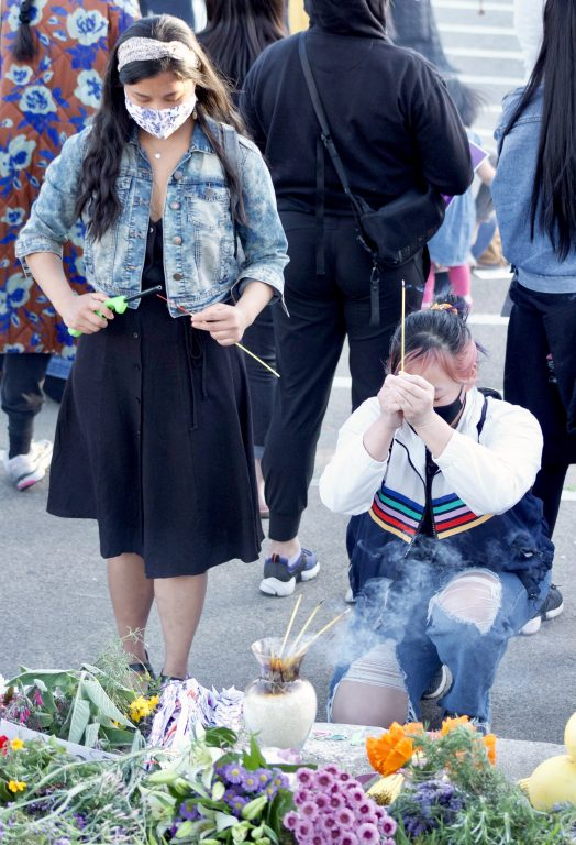 Two young Asian American women offer incense to the victims of the Atlanta shooting.