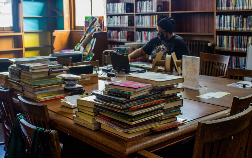 A librarian behind a desk piled high with books
