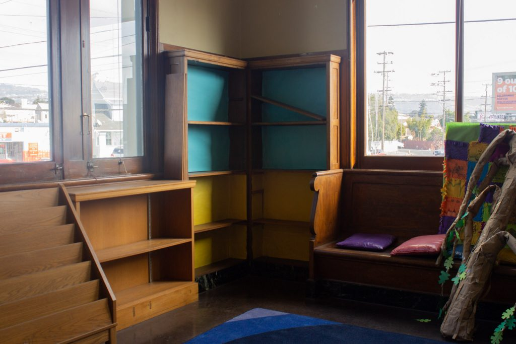 bare wooden bookshelves in the corner of a library