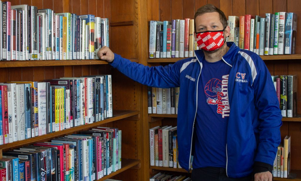 A man wearing blue jacket and red mask posed in front of a big bookshelf in the library.