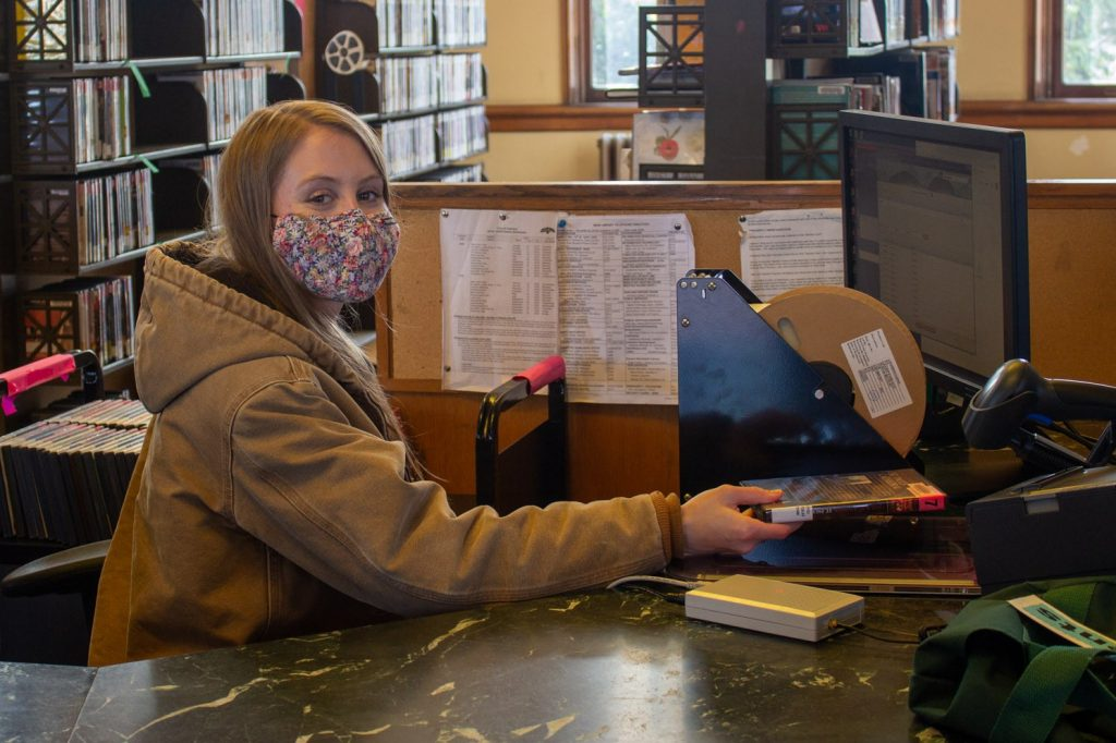 A blond-haired woman sits behind reception desk at library wearing mask and smiling at camera