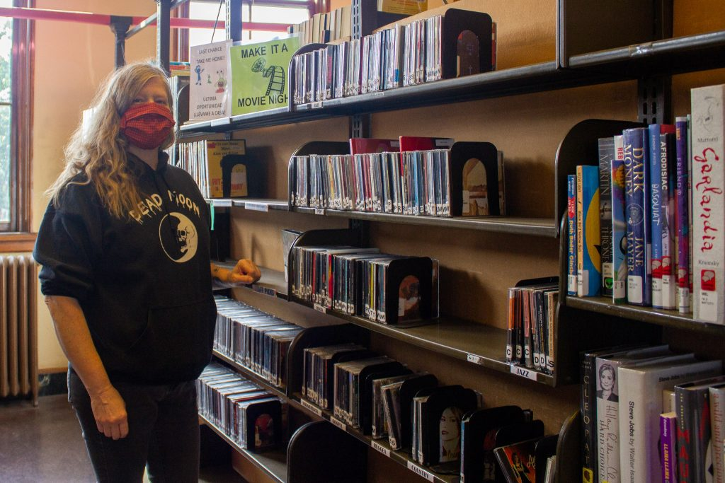 A library worker with wavy blonde hair wearing maroon colored mask and black hoodie stands by big bookshelves