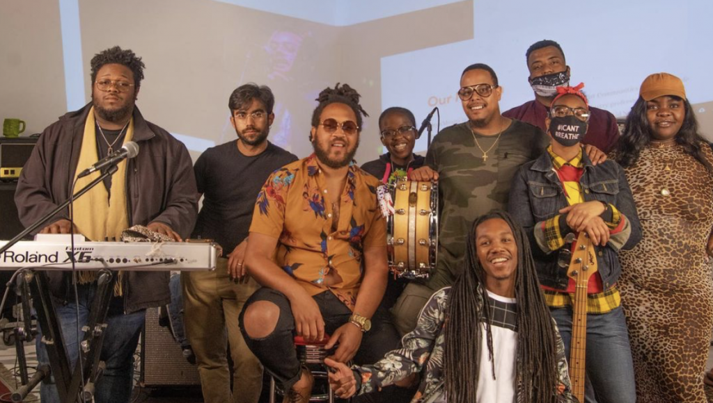 A group of Black and African American people standing near keyboard and other instruments in a band.