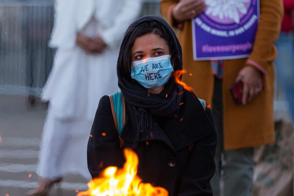 A person wearing a black hooding wears surgical mask with