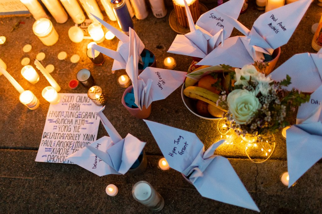image of white paper cranes with names of Atlanta shooting victims and candles surround the cranes