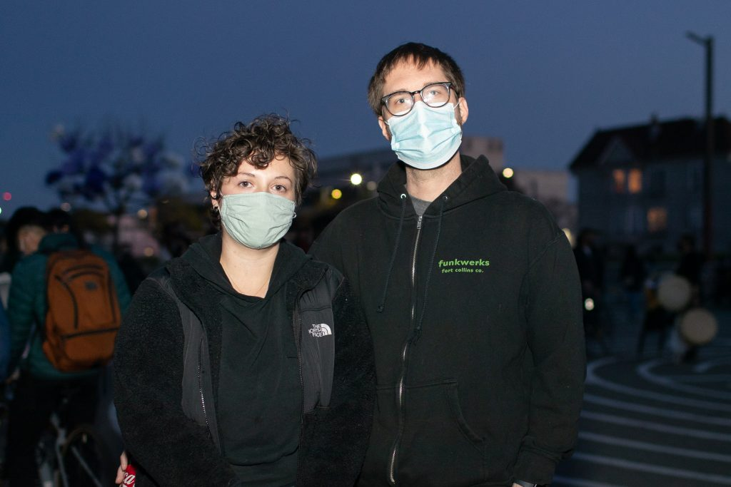A white woman and white man wearing surgical masks pose for photo in the evening at Madison Park in Oakland.