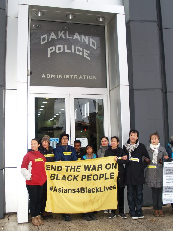 "A group of Asian Americans hold a sign that says ""End the War on Black People"" and #Asians4BlackLives in front of the Oakland Police Department doors."