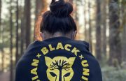 A woman in a forest wearing an Asian Black Unity black hoodie with her back facing camera