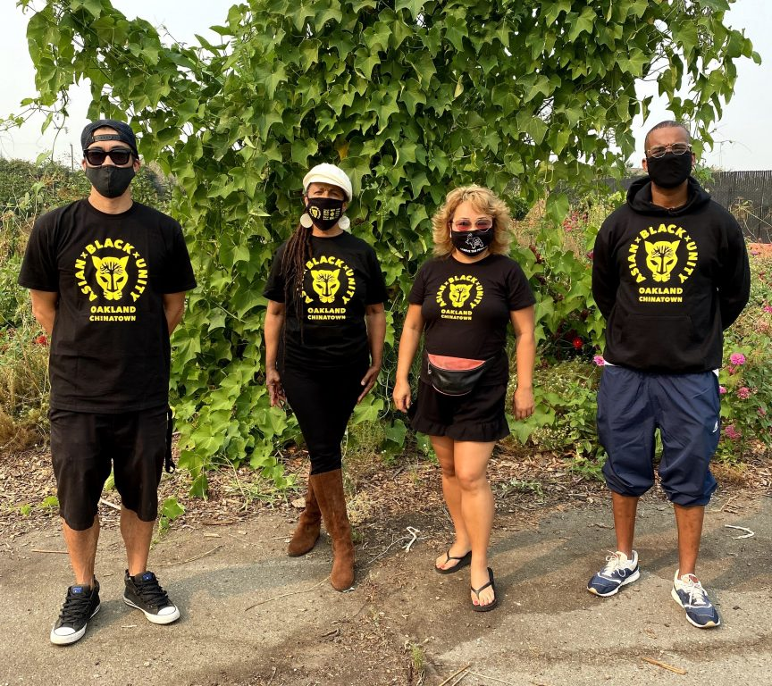 Four people stand in front of some greenery wearing Asian Black Unity t-shirts and face masks