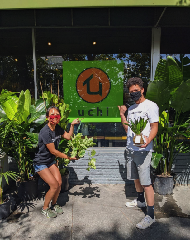 """A Japanese American woman and African American/Filipino plan stand in front of a storefront that says """"Uchi Time"""" with masks and smiles"""