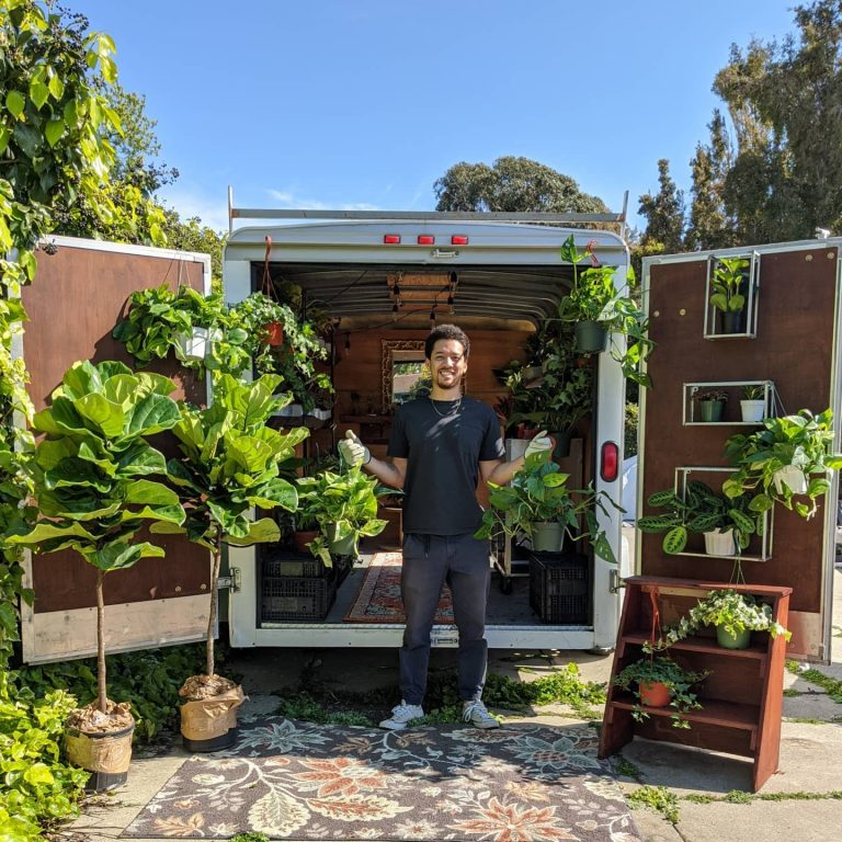 An African American/Filipino man stands in front of a trailer opened in the back that is filled with plants.