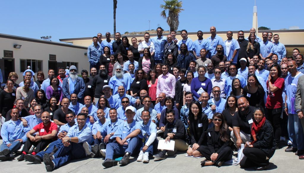 Outside, a large group of people wearing blue garb gather for a photo, including some elected officials and staff from APSC.