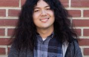 A young man with long, poofy hair stands in front of a brick wall and smiles for the camera.