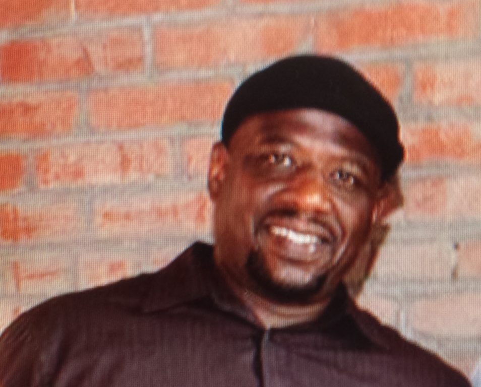 An African American man wearing a small black headpiece smiles in front of a brick wall