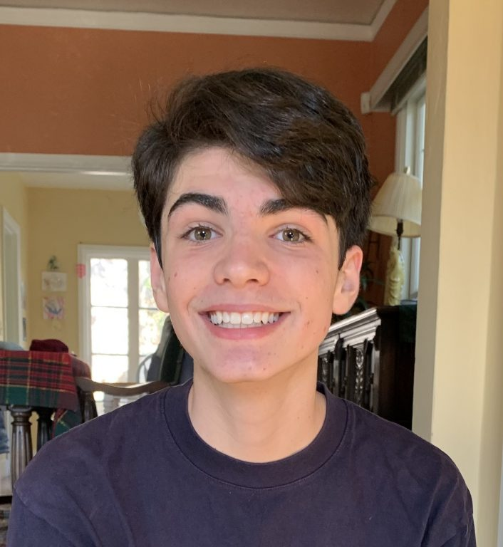 A teenage boy with brown hair smiles for camera