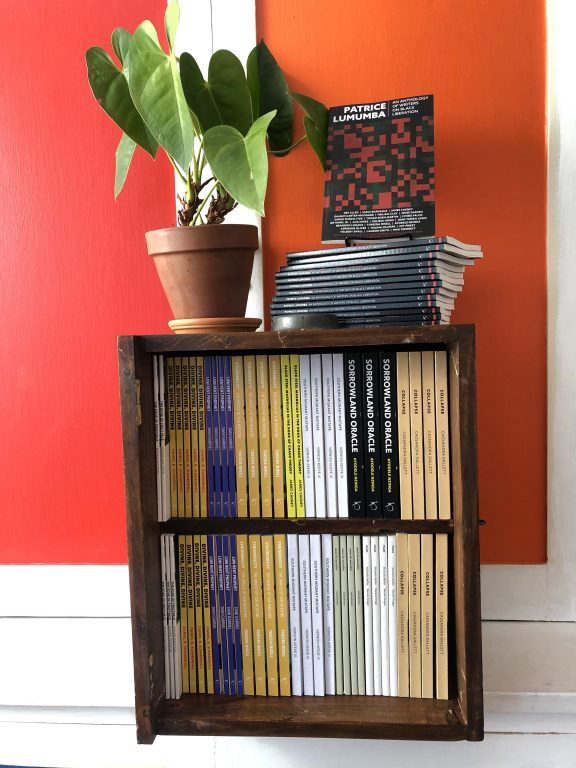 a small bookshelf is filled with new books of poetry and literary arts against a bright red painted wall