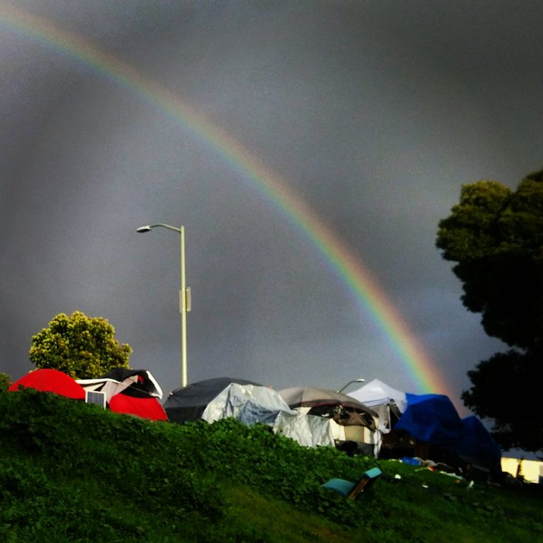 a rainbow over a homeless tent encampment in Oakland
