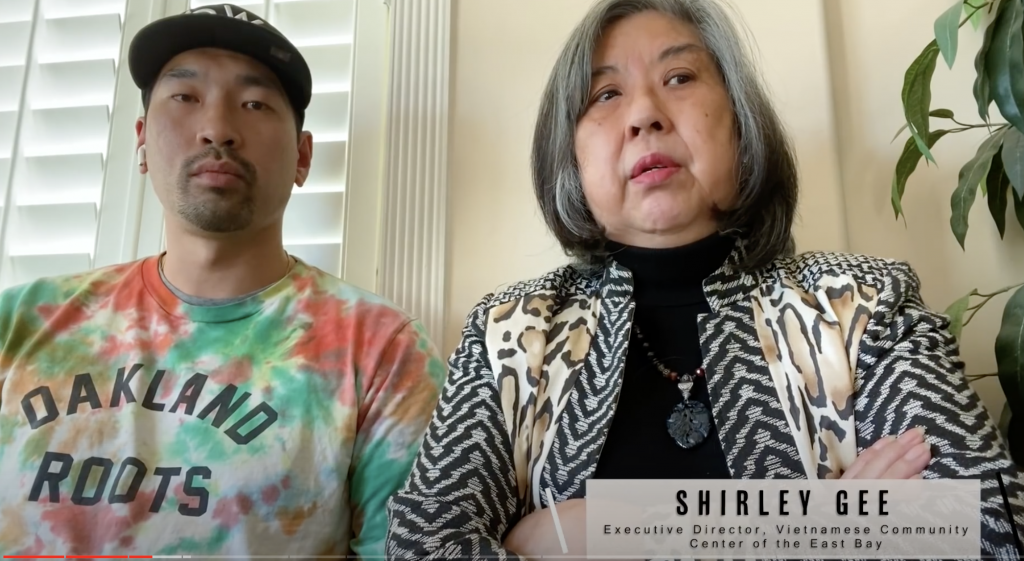 """An Asian American man wearing a tie-dye shirt that says """"Oakland Roots"""" and a woman with a bob haircut and grey hair sit together on a couch."""