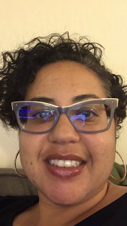 a woman with short brown curly hair, cat-eye glasses, and hoop hearings smiles at camera