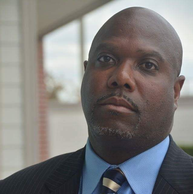A black man wearing a suit and light blue collared shirt looks at the camera