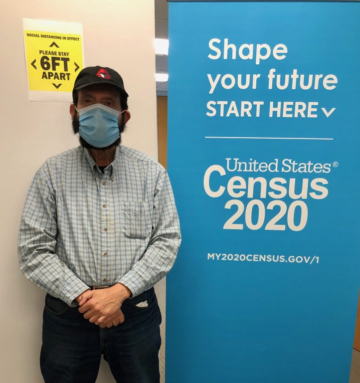 """A 74 year-old man wearing a baseball cap and baby blue surgical mask stands in front of sign that says Census 2020 and :""""six feet apart"""""""