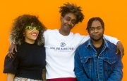 Three Black folks stand against a bright orange background with arms round each other