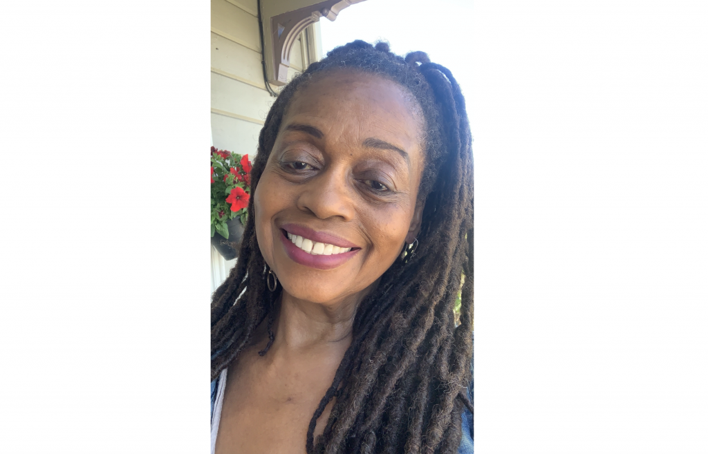 An African American woman with braids smiles for camera