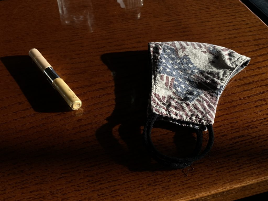 a dark brown wood table has a concealer pen and cloth mask with a faded American flag design