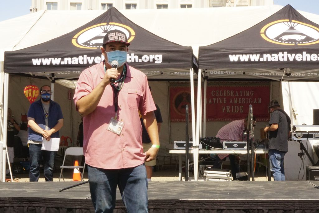 a masked Native American man speaks into a mic in front of a tent that says Native American Health Center