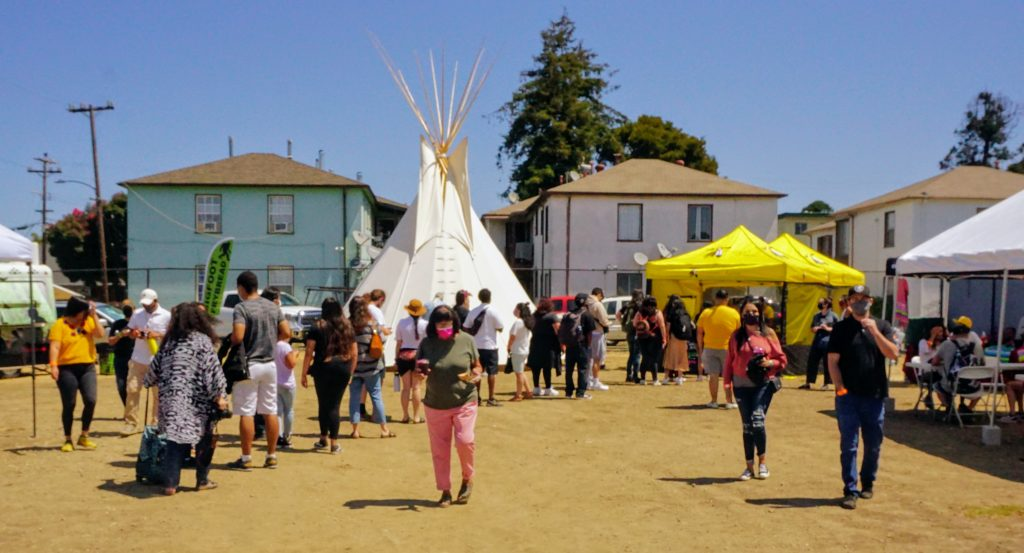 People are milling around outside at an open-air market focusing on Native vendors and services