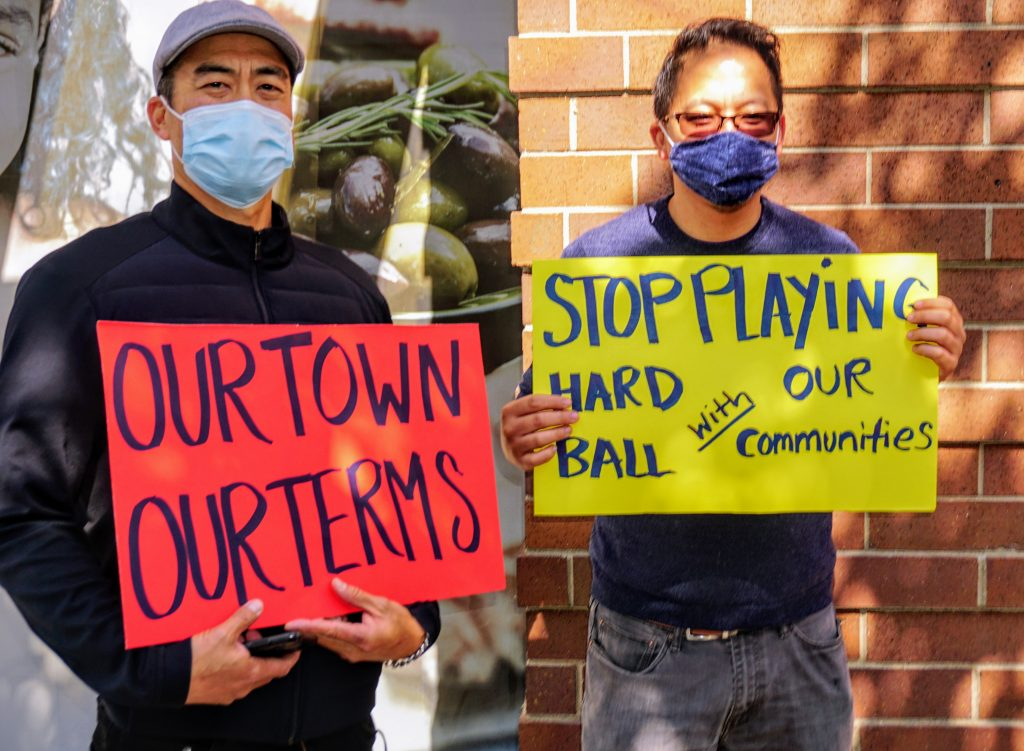 """two Asian American men wearing masks hold signs next to a building that say """"our town our terms."""""""