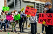 a group of people rally outside a building holding colorful signs with baseball puns asking for benefits to the community