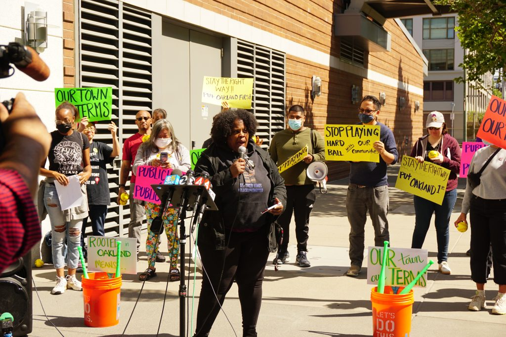 An African American woman speaks into a mic at a rally outside with people behind her holding colorful signs.