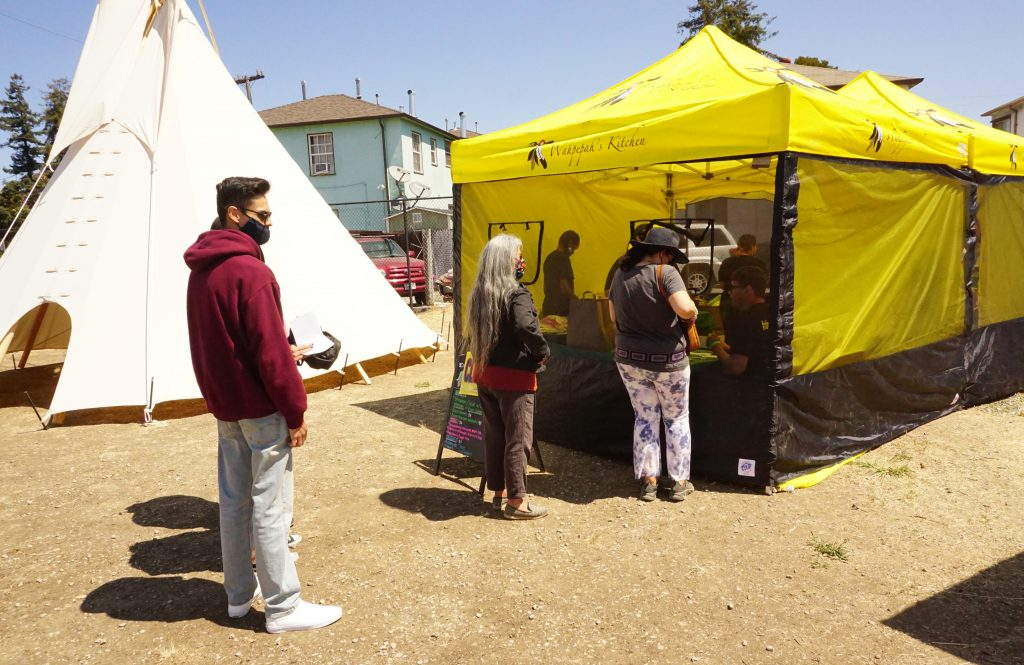 a yellow tent selling Native dishes at the Indigenous Red Market.