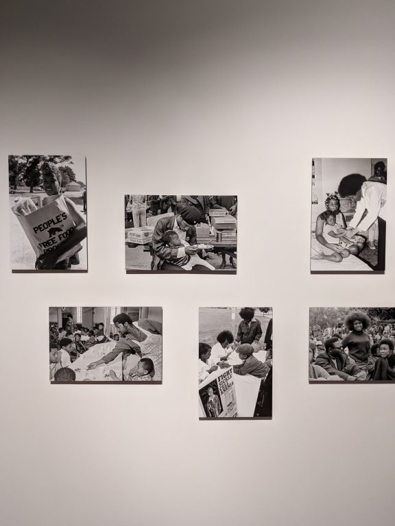 A museum wall with five black and white photos of the Black Panther Party's community programs.