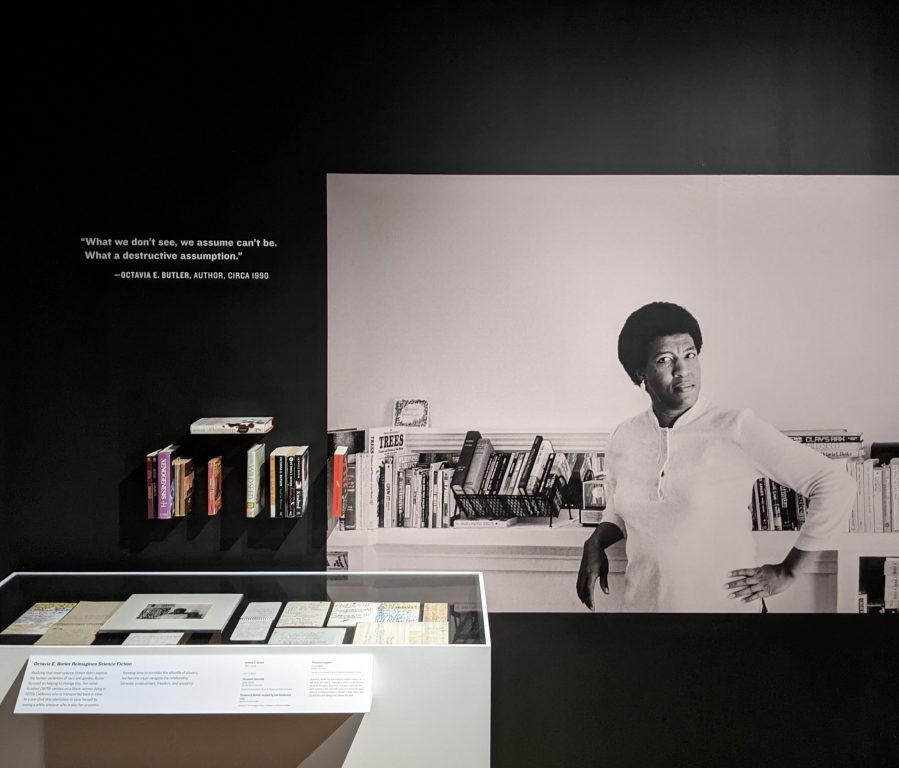 a museum exhibit with a large photo of an African American woman with short hair, writer Octavia Butler.