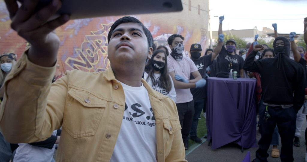 A Latinx youth holds up a screen to take a selfie with a group of people behind him smiling and posing.