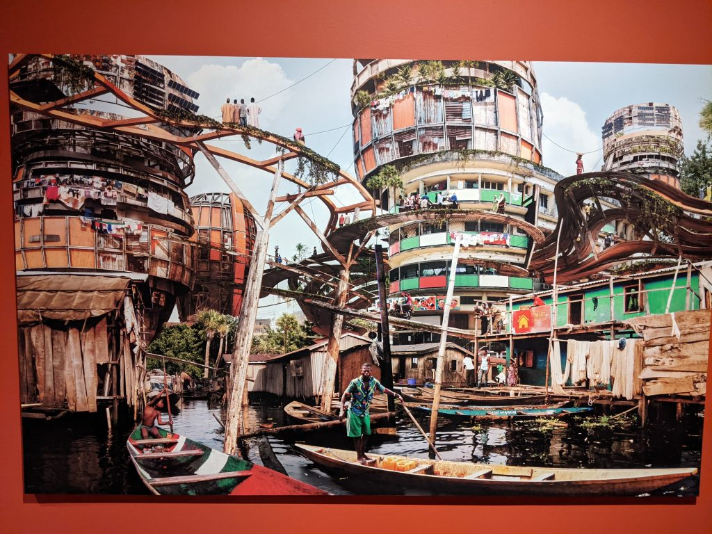 A photo of a large image of shanties and color structures by artist Olalekan Jeyifous.