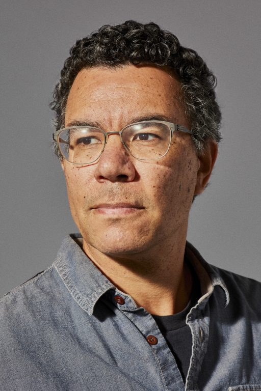 A middle aged man wearing glasses looks into the distance in his headshot.