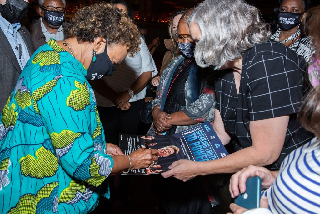 An African American woman with short hair and bright turquoise shirt signs a movie poster.