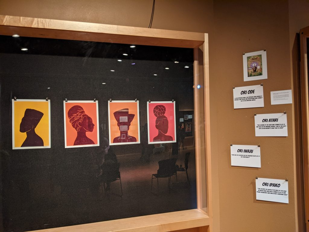 An art exhibit with silhouettes of African American women on display.