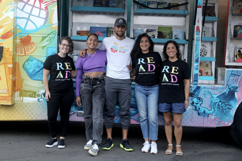 Several smiling people stand casually in front of a colorful mobil bus.