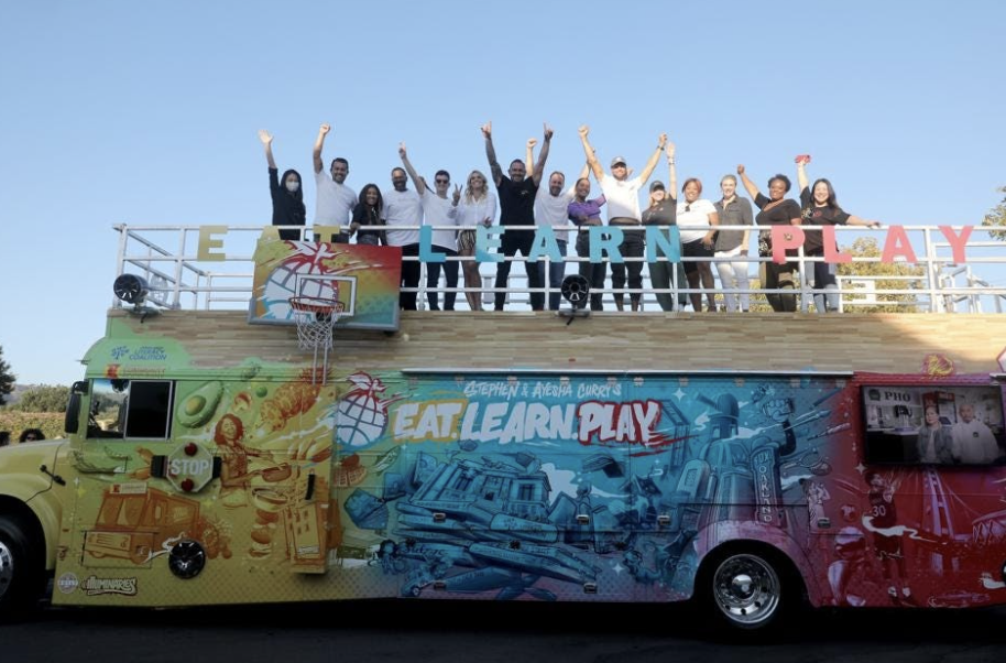 People stand on top of a colorful bus with their hands raised.