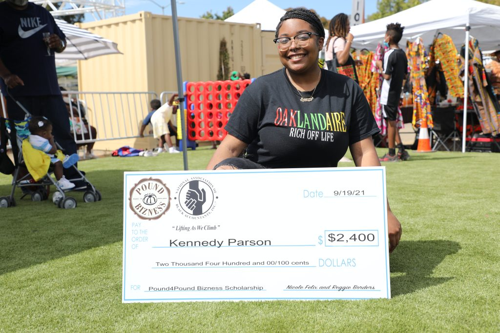 An African American woman holds a large check