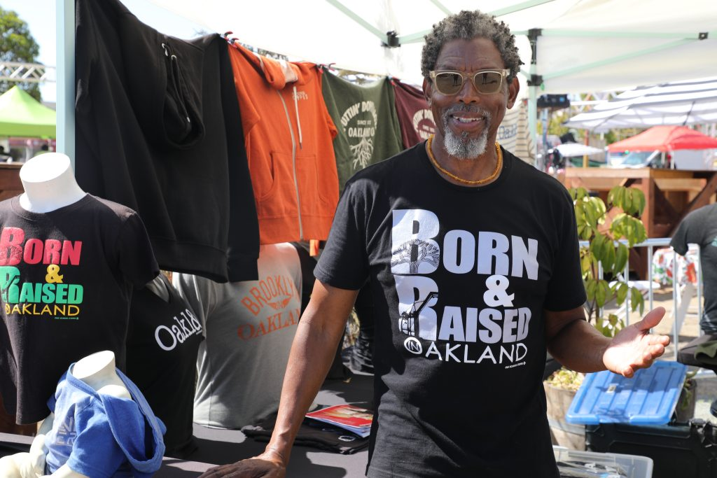 A Black man with short grey hair stands in front of his t-shirt business' stand